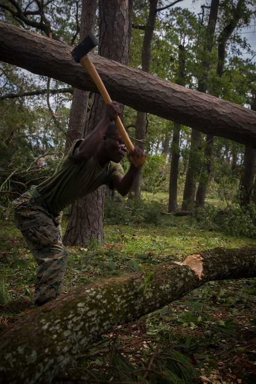 U.S. Marine Corps Lance Cpl. Jordan Thomas with Communications Company, Headquarters Regiment, 2nd Marine Logistics Group, chops a downed tree for removal at Camp Lejeune, N.C., Sept. 17, 2018. Recovery and repair efforts began on base Saturday, September 15, with the majority of efforts focused on clearing roadways and restoring power to critical areas at Camp Lejeune following Hurricane Florence. (U.S. Marine Corps photo by Sgt. Bethanie C. Sahms)