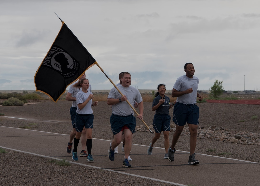 Major Steve Tatro, 49th Wing Comptroller Squadron commander, begins the Prisoner of War/Missing in Action run Sept. 20, at the base track. The Wing Staff Agency was one of the 48 groups to run for half an hour holding the POW/MIA flag. (U.S. Air Force photo by Airman Autumn Vogt)
