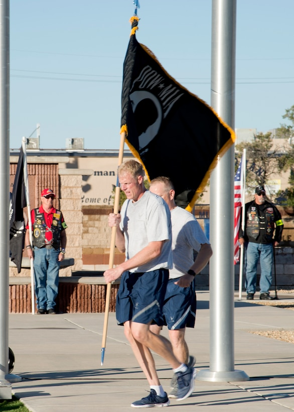 Chief Master Sgt. Timothy Wieser, 635th Material Maintenance Group Chief, runs with the POW/MIA flag during a ceremony at Heritage Park on Holloman Air Force Base, N.M., Sept. 21. The ceremony, in rememberance of prisoners-of-war and those still missing-in-action, was part of Holloman's POW/MIA commemoration. (U.S. Air Force photo by Airman 1st Class Kindra Stewart)