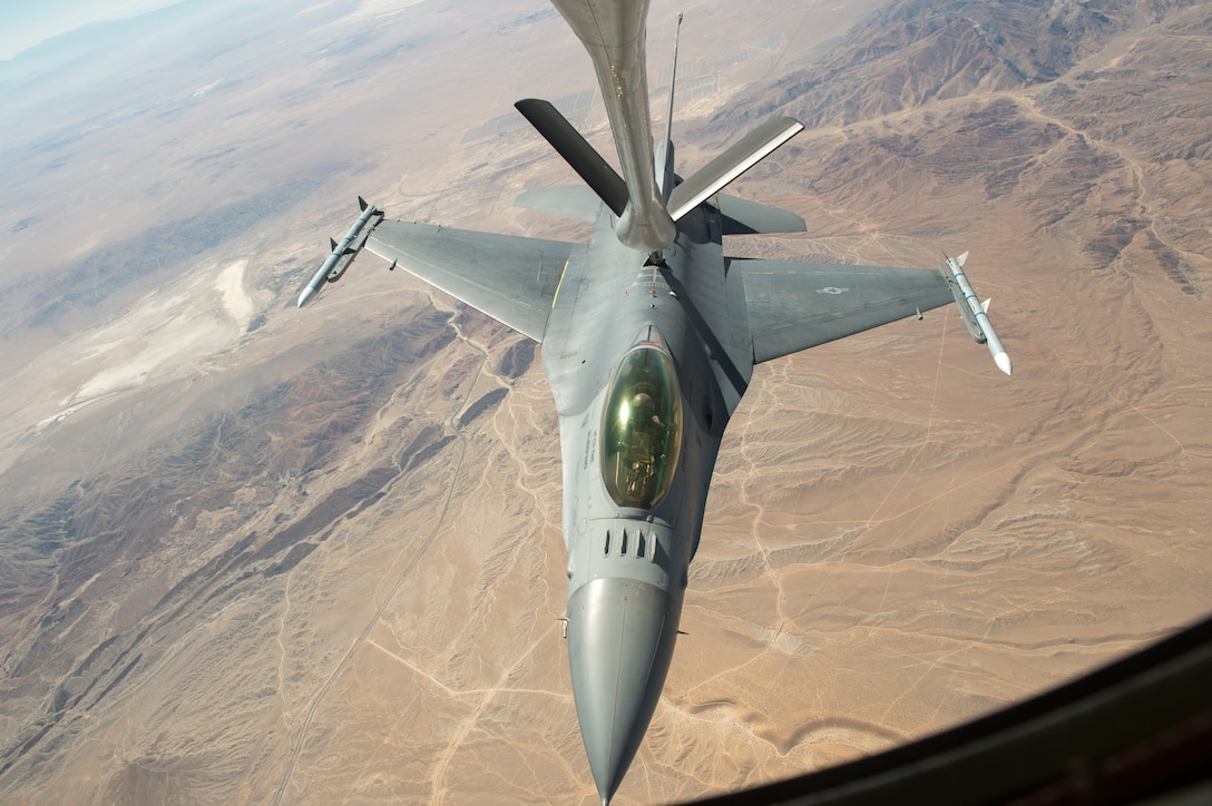 An F-16 Fighting Falcon piloted by Maj. Philip Downing, 416th Flight Test Squadron, receives fuel mid-air from a KC-135 Stratotanker over the California desert Sept. 21, 2018. The ability to conduct aerial refueling is key to the Air Force's Global Reach mission. (U.S. Air Force photo by Kyle Larson)