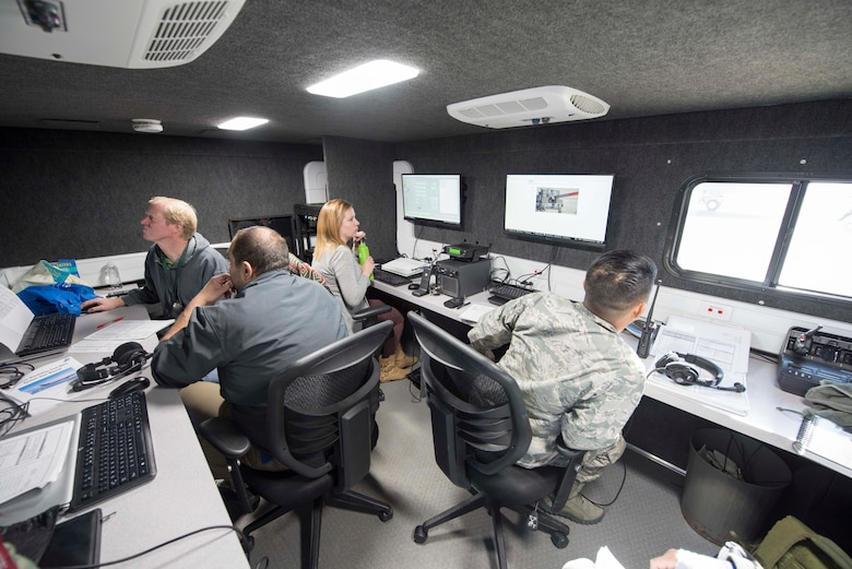 Members from engineering and technical support company JT4 and the 418th Flight Test Squadron sit in the mobile control room of the newly created Receiver Simulation Tool. This is where aerial refueling simulation tests are monitored and recorded. The RST is a ground-based system designed to simulate events that happen during aerial refueling between receiver aircraft and new tankers such as the KC-46 Pegasus, Australian KC-30 and Italian 767. (U.S. Air Force photo by Brad White)