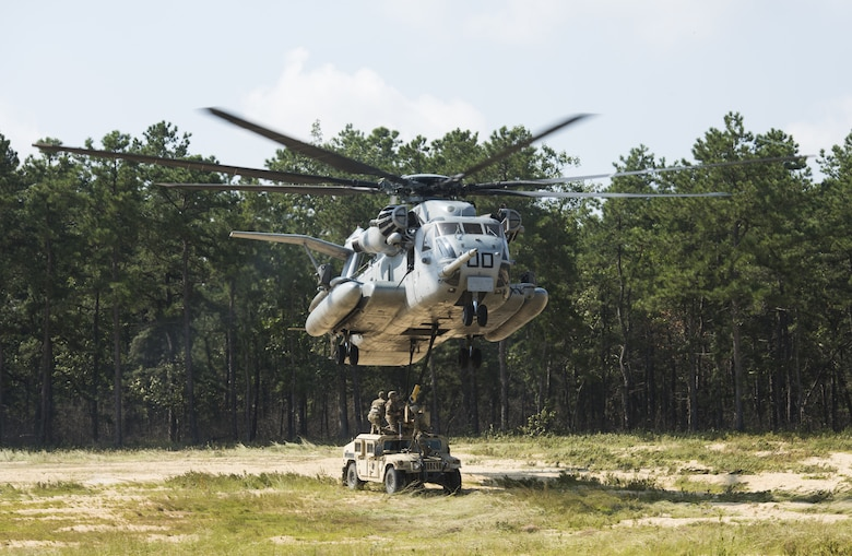 Soldiers with the 101st Airborne Division attach a U.S. Marine Corps CH-53E Super Stallion to a Humvee during a training exercise near Joint Base McGuire-Dix-Lakehurst, New Jersey, Sept. 6, 2018. Once attached, the CH-53E would lift the vehicles in the air then place them back on the ground. The sling load was repeated 10 times on five different vehicles. (U.S. Air Force photo by Airman Ariel Owings)