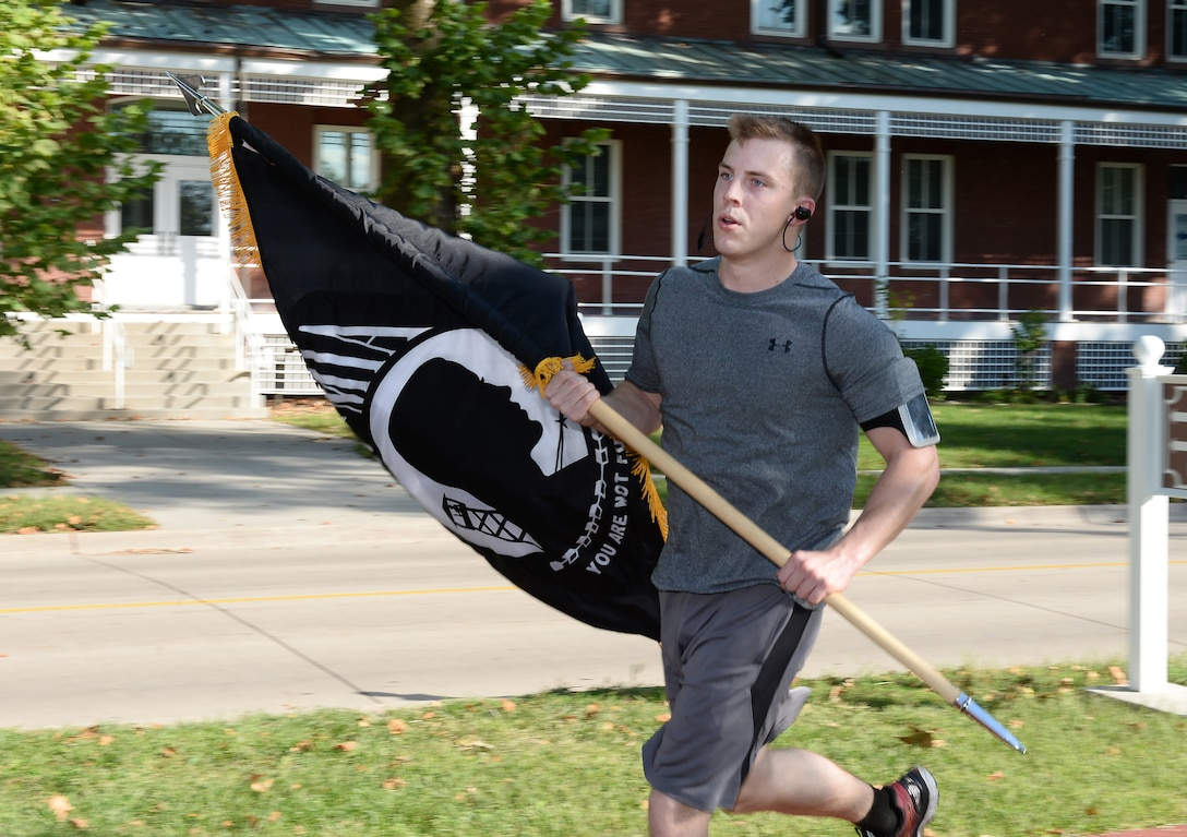 U.S. Air Force Staff Sgt. Matthew Green, 373rd Training Squadron instrument flight control systems instruction, carries the POW/MIA flag during the POW/MIA l 24-Hour Vigil Run Sept. 14, 2018, at Offutt Air Force Base, Nebraska. The United States' National POW/MIA Recognition Day is observed across the nation on the third Friday of September each year. (U.S. Air Force Photo by Charles J. Haymond)