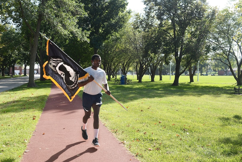 Airman 1st Class Abdulmajid Oamen, 55th Force Support Squadron food service journeymen, runs with the POW/MIA flag during the POW/MIA 24-Hour Vigil Run Sept. 14, 2018, at Offutt Air Force Base, Nebraska. Many Americans across the United States pause on the third Friday of September each year to remember the sacrifices and service of those who were POWs as well as those who are MIA and their families. (U.S. Air Force Photo by Charles J. Haymond)
