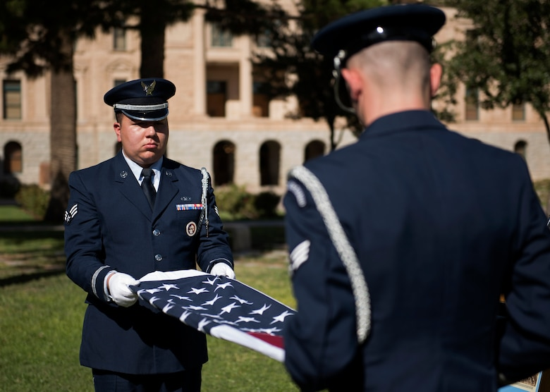 Members of the 56th Fighter Wing honor guard fold a flag to present to Donald Luke, the nephew of WWI fighter ace 2nd Lt. Frank Luke Jr., during a ceremony in his remembrance Sept. 26, 2018, at the state capitol in Phoenix, Ariz. Luke Jr. was killed after refusing to surrender to enemy forces after being shot down in his final mission. (U.S. Air Force photo by Senior Airman Ridge Shan)