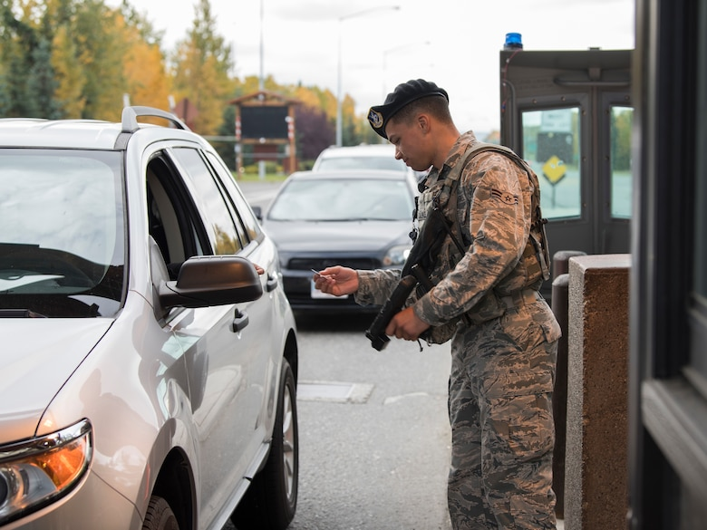 Airman 1st Class Brandon Calwile, a 673d Security Forces Squadron installation entry controller, checks identification at the Boniface Gate at Joint Base Elmendorf-Richardson, Alaska, Sept. 20, 2018. Installation entry controllers provide front-line installation security and must be thorough with every situation at the gates.