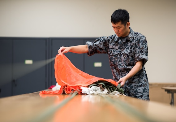 Japanese Air Self-Defense Force Tech. Sgt. Yoshiyuki Nasu, 4th Depot survival equipment maintainer assigned with Iruma Air Base, Japan, inspects a parachute