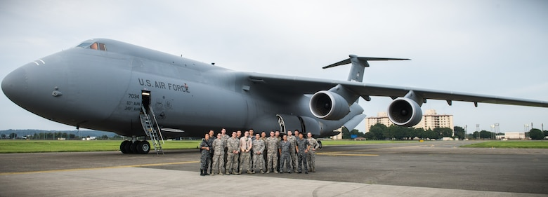 U.S. Air Force and Japan Air Self-Defense Force members pose for a photo in front of a C-5 Super Galaxy