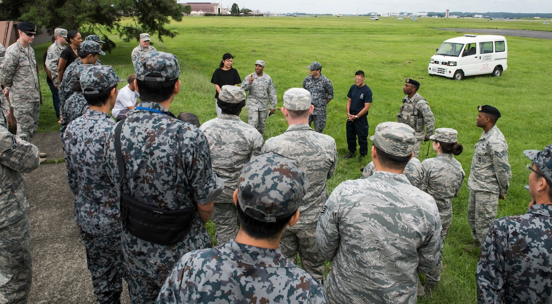 Japan Air Self-Defense Force and U.S. Air Force members listen as Chief Master Sgt. Elvin Young, 374th Airlift Wing command chief, speaks about the Bilateral Exchange Program