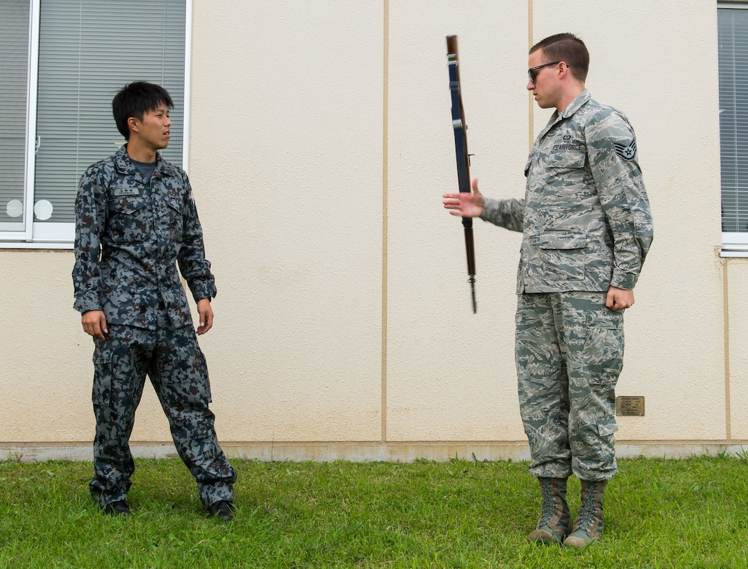 U.S Air Force Staff Sgt. Scott Gricius, 374th Operation Support Squadron weather forecast apprentice, shows Japan Air Self-Defense Force Staff Sgt. Yosuke Tatchiwada, 5th Air Wing airfield coordinator, assigned with Nyutabaru Air Base, Japan, Honor Guard drill movements