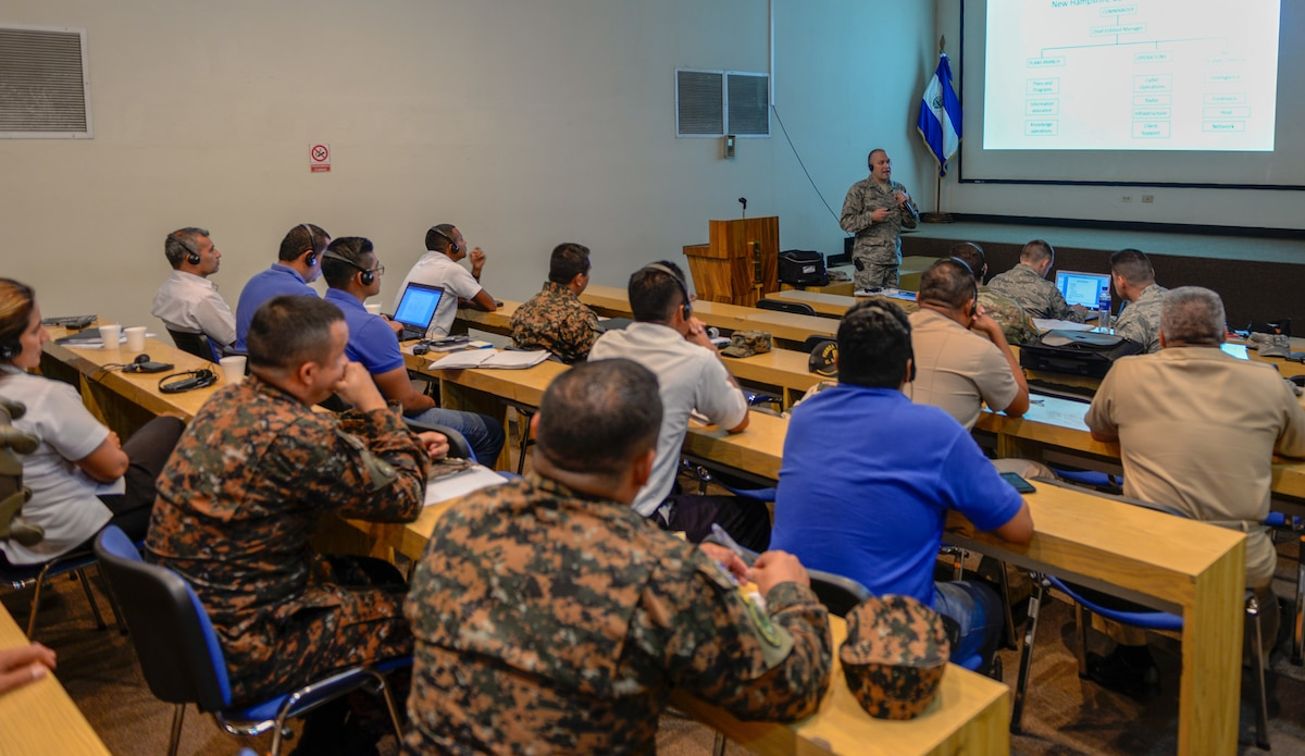Military members sit at desks during a lecture.