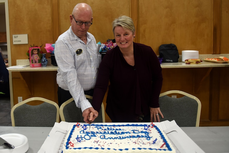 A man in a white button up shirt and a woman in a black blouse cut a cake with white and blue frosting.