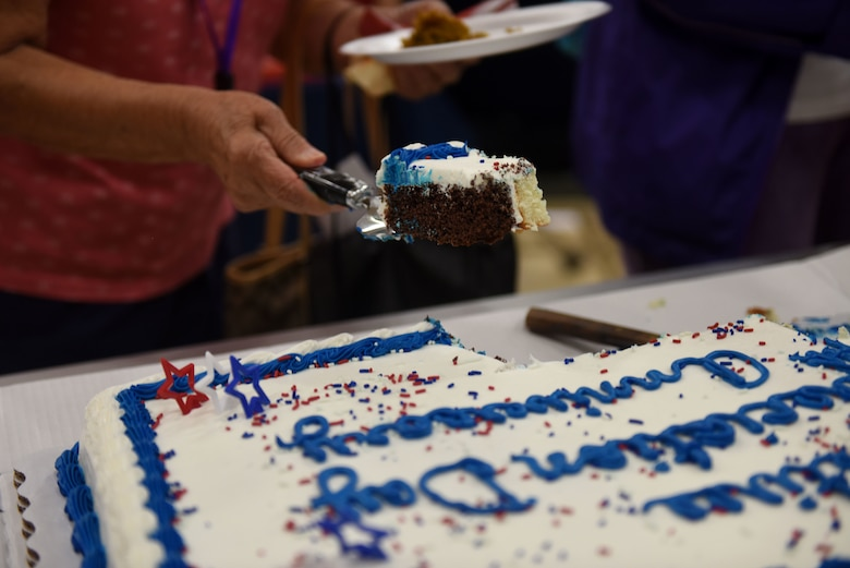A hand lifts up a piece of marble cake with blue and white frosting.