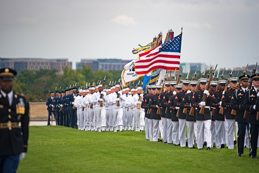 Service members march in formation on a parade field.