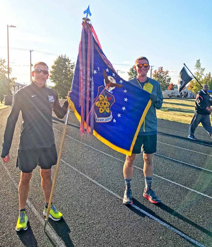 Bruce Robie, left, 225th Support Squadron National Airspace System Defense program manager, and 1st Lt. Krosby Keller, right, 225th Air Defense Squadron air battle manager, proudly hold the Western Air Defense Sector colors after completing 174 miles between them during the Joint Base Lewis-McChord 24-Hour POW/MIA Remembrance Run Sept. 19, 2018.  Keller placed first in individual standings with 100 miles and Robie finished second with 74 miles. (Courtesy photo)