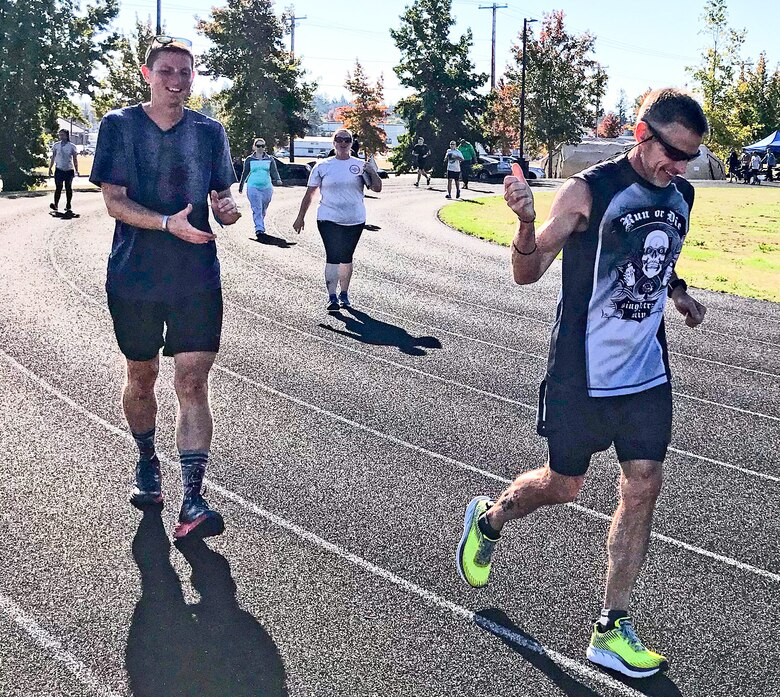 1st Lt. Krosby Keller, left, 225th Air Defense Squadron air battle manager, receives a thumbs up from running partner, Bruce Robie, right, when it was announced that Keller just completed running 100 miles during the 24-Hour POW/MIA Remembrance Run at Joint Base Lewis McChord, Washington, Sept. 19, 2018.  Keller placed first in individual standings with 100 miles and Robie finished second with 74 miles. (Courtesy photo)