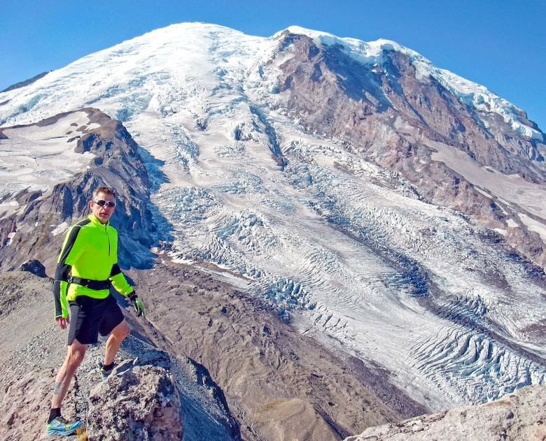 Bruce Robie, 225th Support Squadron National Airspace System Defense program manager, stands at the end of the Third Burroughs Trail in Mount Rainier National Park, Washington, after running the 17-mile trail in four hours, Aug. 31, 2018, in preparation for the POW/MIA Remembrance Run on Joint Base Lewis-McChord.  The trail ends at an altitude of 7,813 feet and consists of a gain and loss of 4,880-feet of elevation.  Participating in extreme sports is not new to Robie who summited Mount Rainier in 2016 with a climbing team.  (Courtesy photo)