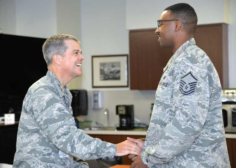 Maj. Gen. John J. DeGoes, 59th Medical Wing commander, presents a command coin to Master Sgt. Andre C. Denson, medical equipment management section chief, at Wilford Hall Ambulatory Medical Center on Joint Base San Antonio-Lackland, Texas, Sept. 17. DeGoes coined Denson for his recent life-saving actions in which he performed the Heimlich maneuver on a patron who was choking in the WHASC's food court area. 