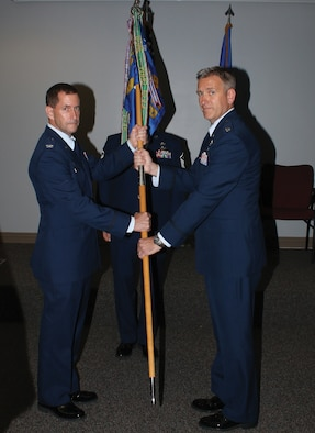 Col. John Robinson, 445th Operations Group commander, passes the guidon to Lt. Col. Brian Quinn, incoming 89th Airlift Squadron commander, during the 89th AS change of command ceremony Sept. 8, 2018