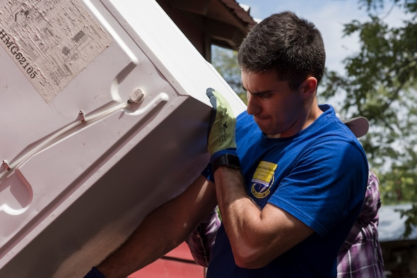 Second Lieutenant Steven Rapphun, 47th Student Squadron student pilot awaiting training, helps remove a flood-damaged refrigerator from a Sonora, Texas, home, Sept. 27, 2018.