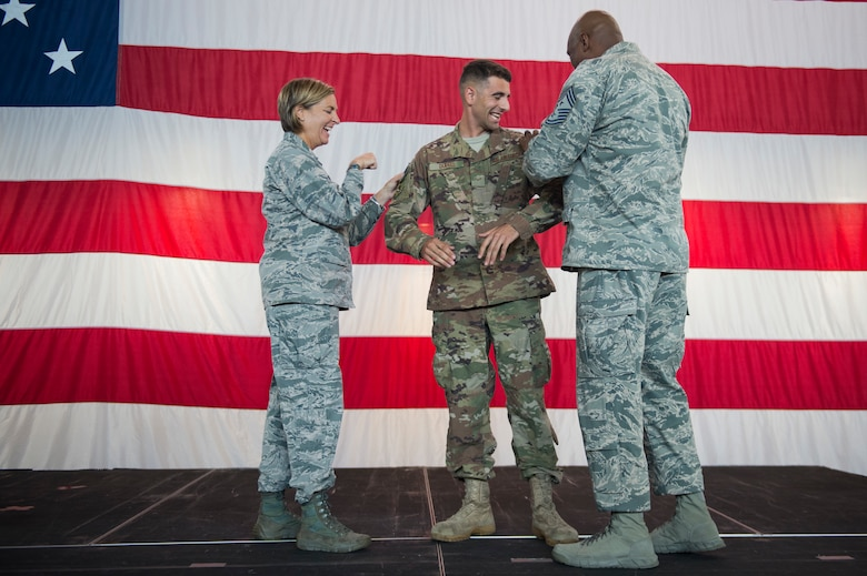 Col. Jennifer Short, 23d Wing commander, and Chief Master Sgt. James Allen, 23d Wing Command Chief, tack on Airman 1st Class Aaron Dupell, 723d Aircraft Maintenance Squadron with senior airman below the zone (BTZ) stripes during a commander's call, Sept. 24, 2018, at Moody Air Force Base, Ga. Senior Airman BTZ promotes an E-3 to E-4 six months earlier than normal and is only given to the most outstanding Airmen. (U.S. Air Force Photo by Andrea Jenkins)