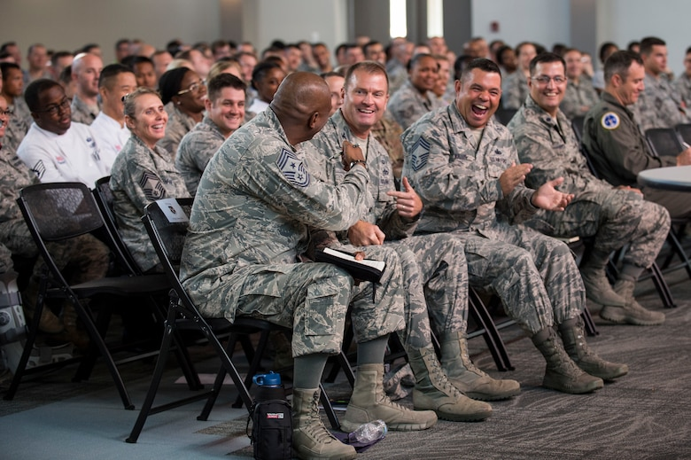 Chief Master Sgt. James Allen, 23d Wing Command Chief, shares a laugh with members of the crowd during a commander's call, Sept. 24, 2018, at Moody Air Force Base, Ga. During a series of commander's calls, the 23d Wing commander updated Team Moody on local and national objectives and initiatives, answered Airmen's questions and highlighted superior performers. (U.S. Air Force photo by Andrea Jenkins)