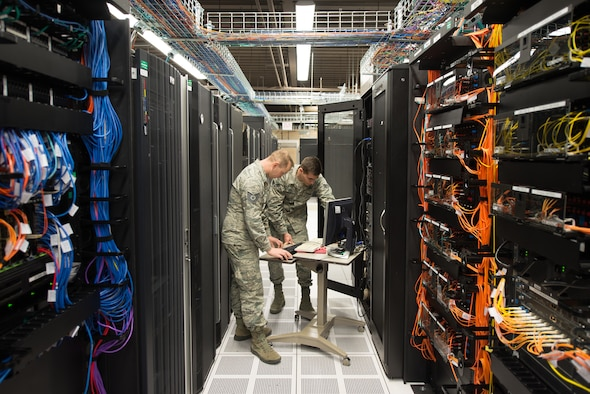 Tech. Sgt. David Mooers and Senior Airman Mario Lunato, 2nd System Operations Squadron system administrators, access one of the core servers in the 557th Weather Wing (WW) enterprise at Offutt Air Force Base, Nebraska, April 27, 2018. The 557th WW's Host Based Security System monitors the servers' overall health and provides security features such as firewalls and antivirus scans that are tailored for the specialized weather systems. (U.S. Air Force photo by Paul Shirk)