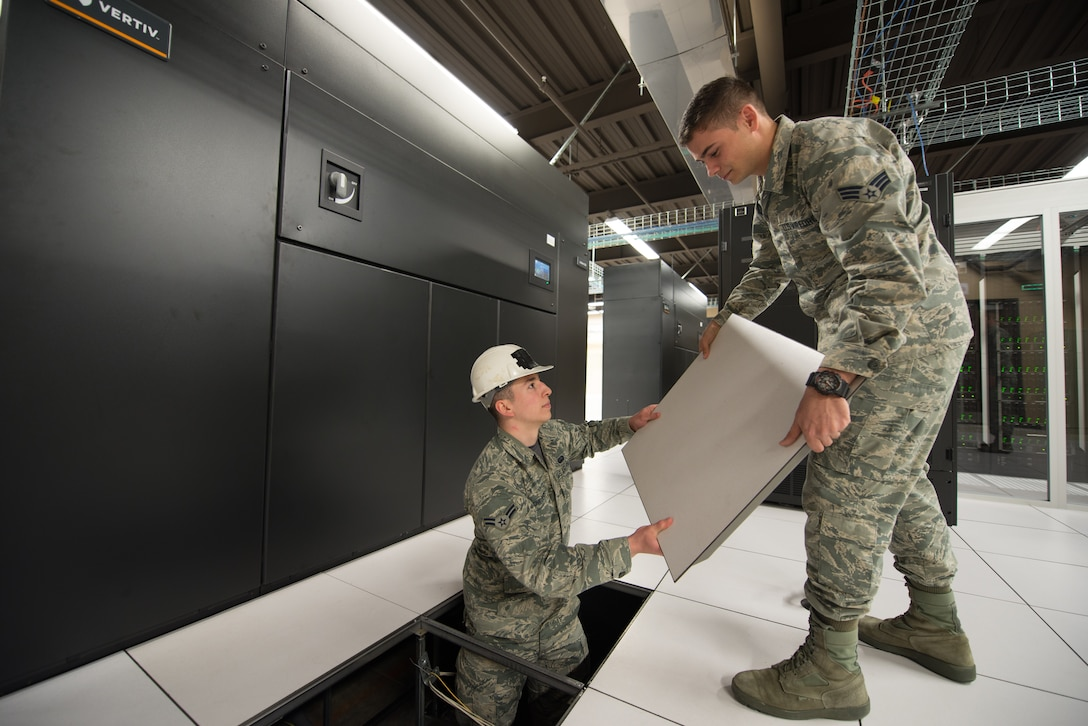 Senior Airman Mario Lunato, 2nd System Operations Squadron system (SYOS) administrator and Airman 1st Class Caleb Childers, 2nd SYOS cyber surety technician, replace a flooring panel next to a computer room air conditioner (CRAC) in the 557th Weather Wing's High Performance Computer Data Center at Offutt Air Force Base, Nebraska, April 27, 2018. The CRACs were replaced as part of a $4 million plan to improve the data center's cooling capabilities. (U.S. Air Force photo by Paul Shirk)