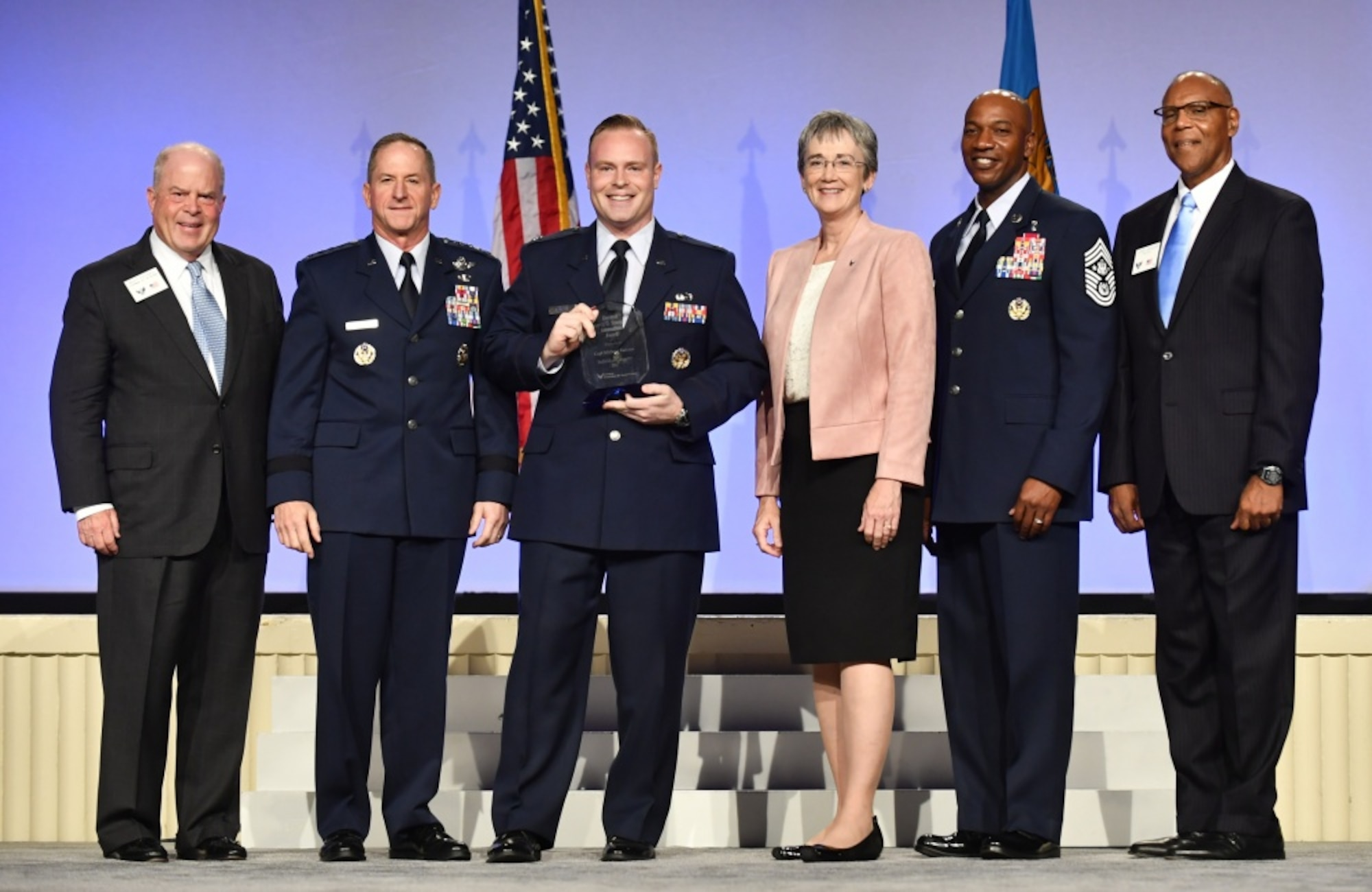 Capt. Michael Kanaan, intelligence, surveillance and reconnaissance enterprise lead receives the Gen. Spencer Innovation Award - Individual from Chief of Staff of the Air Force Gen. David L. Goldfein, second from left, Secretary of the Air Force Heather Wilson, third from right, Chief Master Sgt. of the Air Force Kaleth Wright, second from right, Gen. (ret.) Larry Spencer, far right, and Whit Peters, Chairman of the Air Force Association Board, far left, during the AFA Air, Space and Cyber Conference in National Harbor, Md., Sept. 17, 2018. The award recognizes Kanaan in government, industry and academia as a thought leader in the digital field across all Air Force functions who demonstrably shapes the highest levels of operations, messaging and funding. (U.S. Air Force photo by Staff Sgt. Rusty Frank)