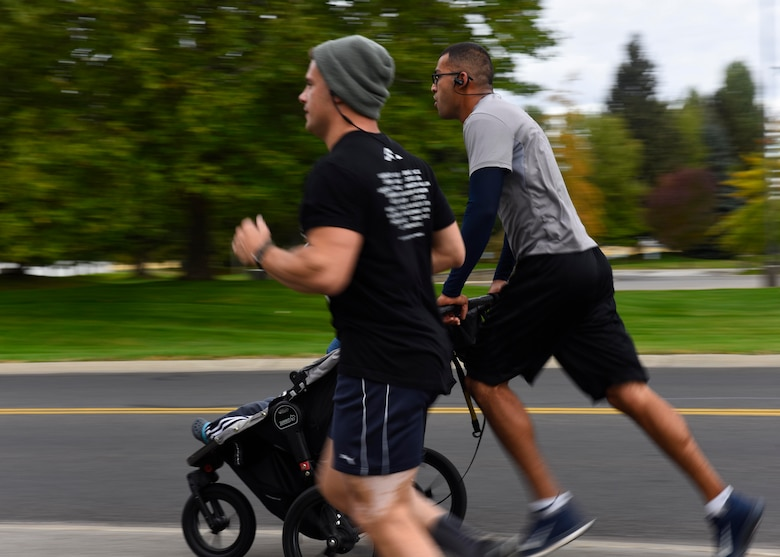 Senior Master Sgt. Jorge Rivera, 92nd Operation Support Squadron air traffic controller, pushes a stroller during the CMSAF Binnicker 9K Memorial Run at Millier Park in Farichild Air Force Base, Washington, Sept. 22, 2018. Participants of the run received a finisher's medallion as well as a commemorative event challenge coin. (U.S. Air Force photo/Airman 1st Class Lawrence Sena)
