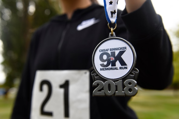 Airman 1st Class Desteny Zuniga, 92nd Comptroller Squadron unit manager, holds up a finisher's medallion she received after running the CMSAF Binnicker 9K Memorial Run at Miller Park in Fairchild Air Force Base, Washington, Sept. 22, 2018. The AFEV is a nonprofit organization whose mission is to provide a safe and secure home for surviving spouses of retired enlisted Airmen. (U.S. Air Force photo/Airman 1st Class Lawrence Sena)