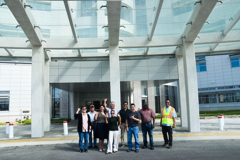 Elisa Beck (center), Resident Engineer, Medical Resident Engineer, stands with her team in front of the new Brian Allgood Army Community Hospital, Camp Humphreys, South Korea, Sep. 7.