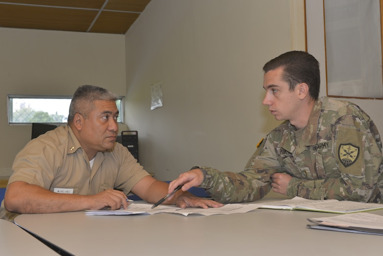 A New Hampshire Army National Guard Soldier speaks with a Salvadoran navy officer.