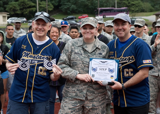 U.S. Air Force Staff Sgt. Kristie Hardinger, center, with the 51st Logistics Readiness Squadron, receives a certificate of promotion from Col. William Betts, right, 51st Fighter Wing commander, at Osan Air Base, Republic of Korea, Sept. 28, 2018. Hardinger was promoted to technical sergeant thorough the Stripes to Exceptional Performers program. (U.S. Air Force photo by Staff Sgt. Sergio A. Gamboa)