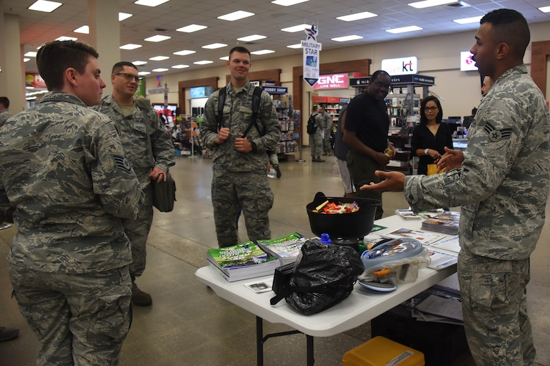 U.S. Air Force Senior Airman Christopher Montgomery, far right, emergency manager with the 51st Civil Engineer Squadron emergency management office, informs Osan personnel about the importance of being prepared for natural disasters at Osan Air Base, Republic of Korea, Sept. 14, 2018. Emergency management personnel set up booths around the base to recognize National Preparedness Month. (U.S. Air Force photo by Tech. Sgt. Ashley Tyler)