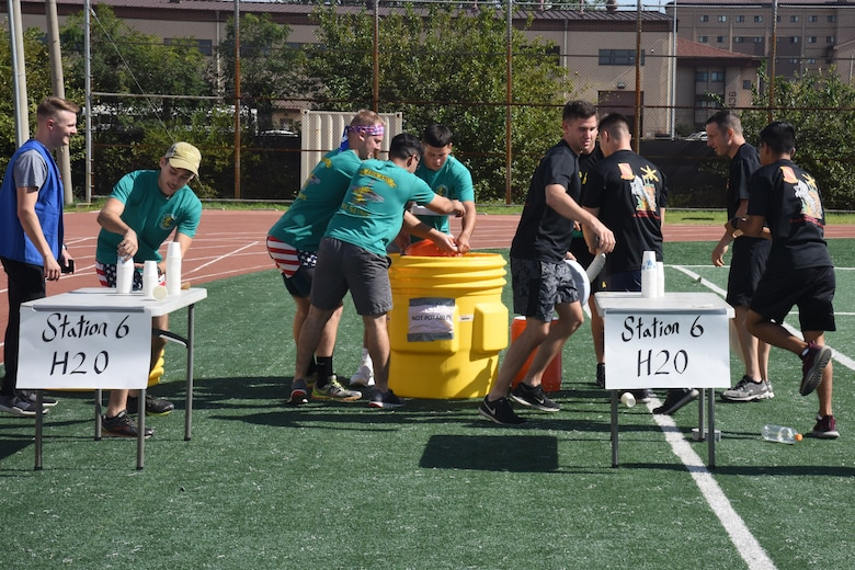U.S. Air Force 25th Fighter Squadron personnel, left, compete with U.S. Army 35th Air Defense Artillery Brigade personnel to fill a water cooler during the Mustang Challenge relay at Osan Air Base, Republic of Korea, Sept. 27, 2018. The 1.7-mile relay was a combined idea from 51st Civil Engineer Squadron emergency management and Osan Red Cross, where teams ran a six-station course focusing on disaster preparation skills.(U.S. Air Force photo by Tech. Sgt. Ashley Tyler)