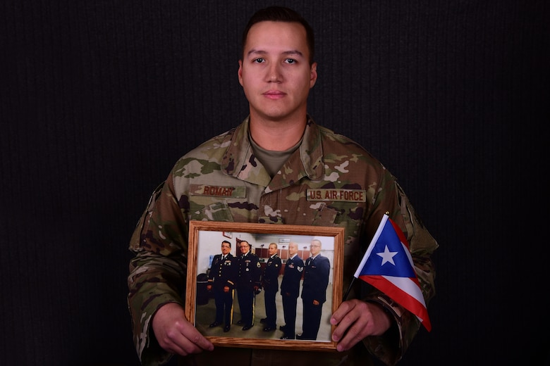 U.S. Air Force 1st Lt. Jorge Roman-Castillo, 386th Air Expeditionary Wing Sexual Assault Response Coordinator, poses with a photo of his family Sept. 27, 2018, at an undisclosed location in Southwest Asia. Roman-Castillo, a fourth-generation veteran, said his upbringing of respect has proved critical to his effectiveness as a SARC and an Air Force officer. (U.S. Air Force photo by Staff Sgt. Christopher Stoltz)