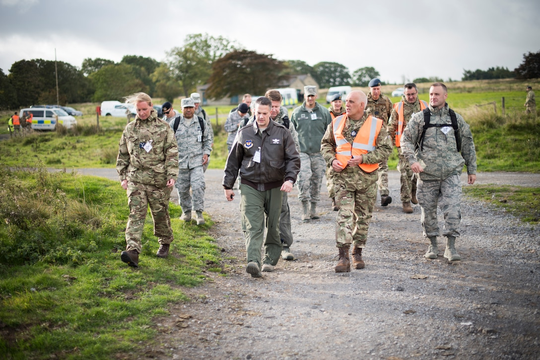 U.S. Air Force Airmen speak with Royal Air Force airmen about emergency procedures during an exercise at a training filed near RAF Leeming, England, Sept. 26, 2018. The scenario tested emergency responses of multiple agencies to a simulated military aircraft crash in the Northeast area of RAF Leeming's area of responsibility and a fuel spill at RAF Waddington. (U.S. Air Force photo by Tech. Sgt. Emerson Nuñez)