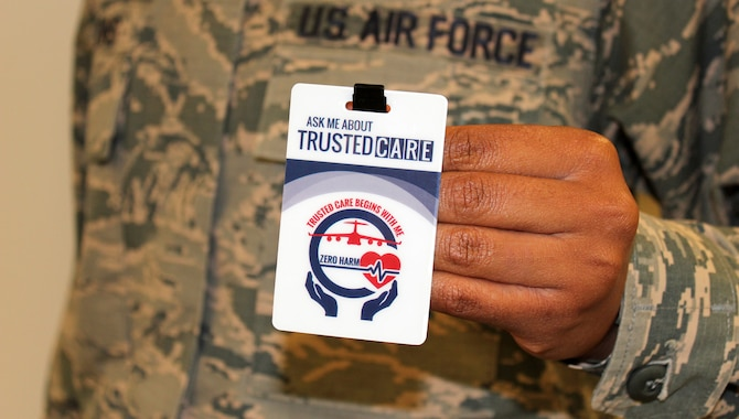 An Airman holds up his Trusted Care badge at the Defense Health Headquarters.