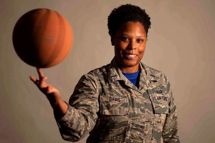 A female airman spins a basketball on her finger.