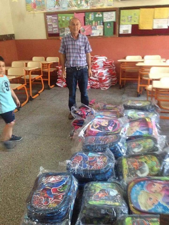 A teacher at Necmiye CoskunTuncel Ilkokulu Primary School receives backpacks and other school supplies for local Turkish students before the first day of school in Adana, Turkey.