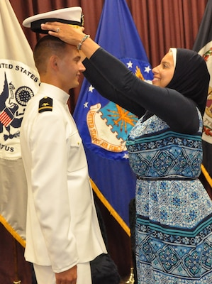 """IMAGE: DAHLGREN, Va. (Sept. 11, 2018) – Nourhan Ibrahim places a new officer's cover on the head of her husband, Dillard Patton, who was commissioned into the Naval reserves as an ensign at a ceremony held at the Aegis Training and Readiness Center. Ensign Patton - an NSWCDD System Safety Engineering Division civilian engineer – expressed a special appreciation to his family during the ceremony. """"Without your support, I wouldn't be standing where I am today,"""" said Patton. """"You have stood by my side through my best and my worst, but in all instances you motivated me to give it my all and succeed."""""""