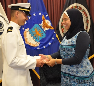 """IMAGE: DAHLGREN, Va. (Sept. 11, 2018) – U.S. Navy Ensign Dillard Patton presents a Navy spouse coin to his wife, Nourhan Ibrahim, moments after he was commissioned into the Naval reserves as an ensign. The NSWCDD System Safety Engineering Division civilian engineer expressed a special appreciation to his wife, son, and all his family during the ceremony. """"Without your support, I wouldn't be standing where I am today,"""" said Patton. """"You have stood by my side through my best and my worst, but in all instances you motivated me to give it my all and succeed."""""""
