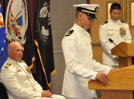 """IMAGE: DAHLGREN, Va. (Sept. 11, 2018) - U.S. Navy Ensign Dillard Patton speaks to family, friends, and coworkers at his commissioning ceremony held at the Aegis Training and Readiness Center. Moments earlier, the NSWC Dahlgren Division System Safety Engineering Division civilian engineer was commissioned into the officer ranks of the Naval reserves through the Direct Commission Officer program. """"We are victorious because we are faithful to these core values (honor, courage, and commitment) not only when serving on official duty, but also in our personal lives,"""" Patton told his audience, including Capt. Andrew Thomson, commissioning officer, left, and Lt. Cmdr. Warren Bong, master of ceremony. """"I encourage every individual in this room to consider how these (U.S. Navy) core values impact your lives."""""""