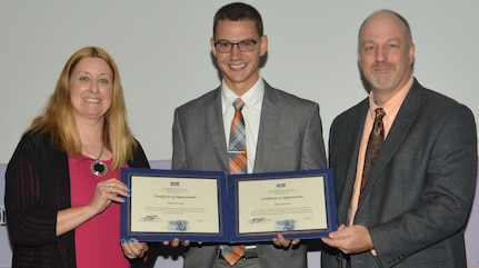 IMAGE: DAHLGREN, Va. (Sept. 21, 2018) – Dillard Patton receives certificates of appreciation from Naval Surface Warfare Center Dahlgren Division (NSWCDD) Acting Chief of Staff Terri Gray and Acting Deputy Technical Director Chris Clifford at the 2018 NSWCDD Academic Recognition Ceremony. Patton – commissioned into the Naval Reserves ten days earlier – was recognized for completing two professional certifications. He received a system safety certification from the University of Southern California and an associate systems engineering professional certification from the International Council on Systems Engineering.