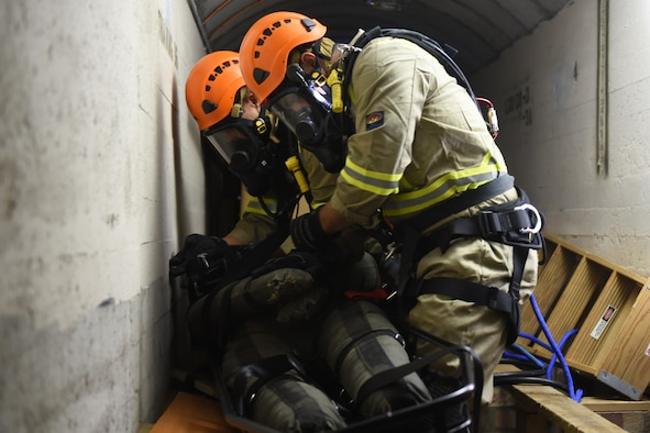 48th Civil Engineer Squadron firefighters simulate recovering a patient during a confined space training exercise Royal Air force Lakenheath, England, Sept. 24. Confined-space rescue becomes necessary when someone becomes trapped in areas such as tanks, vaults and tunnels. (U.S. Air Force photo/ Christopher S. Sparks)