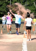 Volunteers  throw different colors of chalk toward runners during the sixth annual color run Sept. 22, 2018, at Columbus Air Force Base, Mississippi. The 14th Force Support Squadron Youth Center hosted the Color Run as fun way for Airmen to be healthy and stay fit.  (U.S. Air Force photo by Airman Hannah Bean)