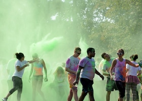 Participants walk away covered in a rainbow of color after the sixth annual color run Sept. 22, 2018, at Columbus Air Force Base, Mississippi. Over 28 volunteers helped ensure color run participants were safe and had fun. (U.S. Air Force photo by Airman Hannah Bean)