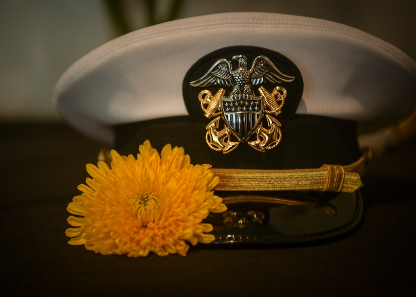 A yellow flower, signifying remembrance, rests next to a naval dress cap during the Bells Across America memorial ceremony Sept. 27, 2018, at Joint Base Charleston, S.C. The ceremony is an annual U.S. military tradition held across the country to honor and commemorate fallen service members. During the ceremony, a bell is rung after each service member's name is read.
