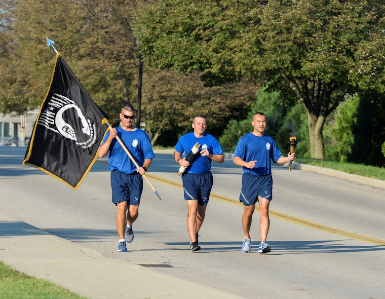 Members of the Wright-Patterson Chiefs Group run the last leg of the POW/MIA 24-hour run and overnight vigil at Wright-Patterson Air Force Base, Ohio, Sept. 21, 2018. The run concluded at the base POW/MIA wreath laying ceremony. (U.S. Air Force photo/Wesley Farnsworth)